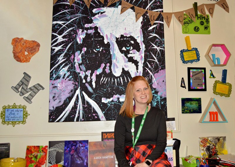 Heather McCutcheon sits in her classroom in front of a wall of artwork.