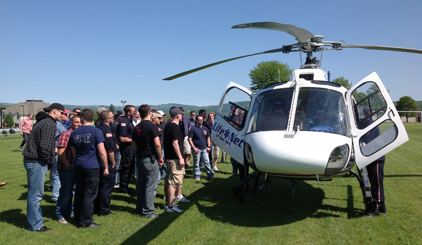 Students learning outside near helicopter